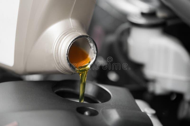 Schließen Sie oben und Motorenöl zum Automotor gießen lizenzfreie stockfotos