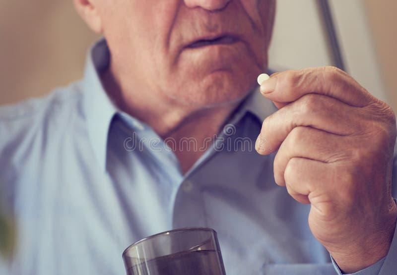Schließen Sie oben vom älteren Mann, der zu Hause Medizinpille nimmt Abgetöntes Foto stockfotografie