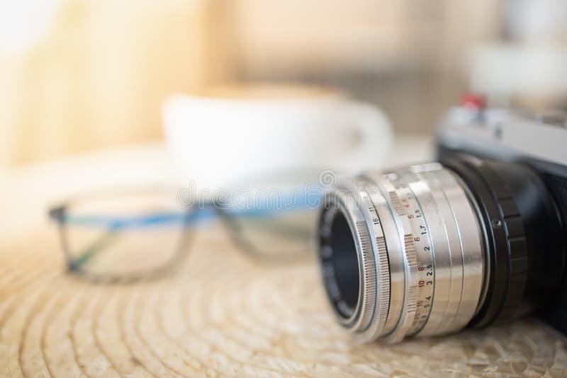 Schließen Sie oben vom altem und WeinleseKameraobjektiv mit Lesebrille und weißem Tasse Kaffee stockfotografie