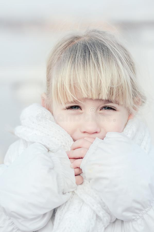 Schließen Sie oben vom attraktiven blonden Mädchen, das auf der Straße am kalten eisigen Tag schnarcht und versucht, warm zu erha stockbilder