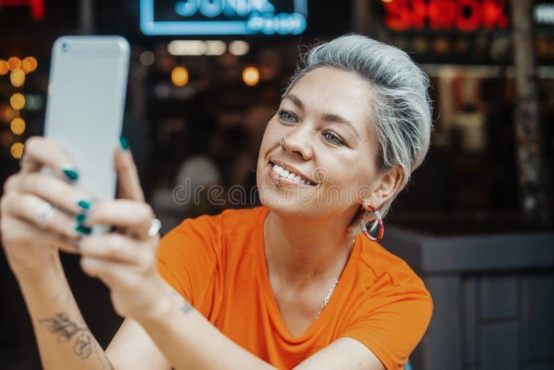 Schließen Sie oben vom attraktiven blonden Mädchen im orange T-Shirt, das selfie am Café macht lizenzfreies stockbild