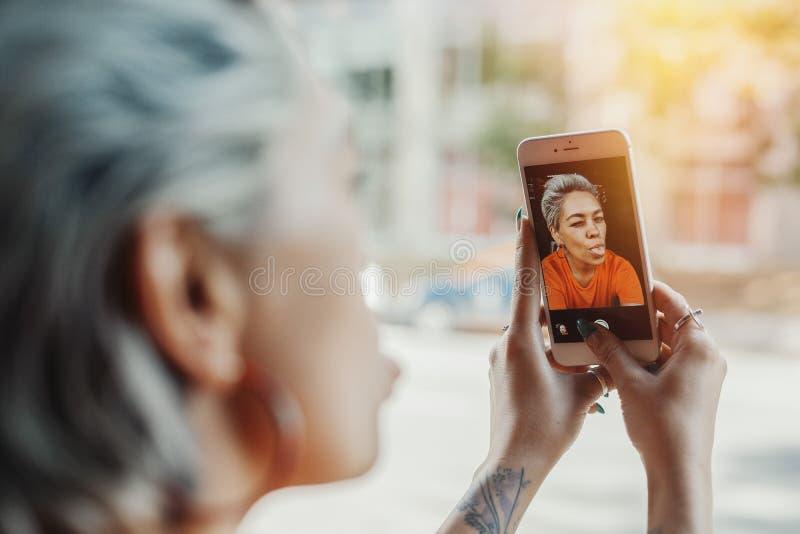 Schließen Sie oben vom attraktiven herrlichen blonden Mädchen im orange T-Shirt, das selfie macht stockfotografie