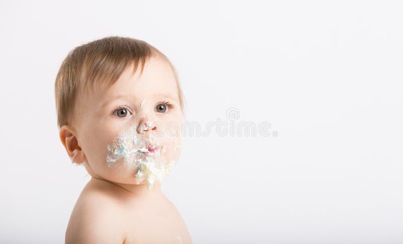 Schließen Sie oben vom Baby mit dem Gesicht, das vom Kuchen und vom Bereifen voll ist lizenzfreie stockfotografie