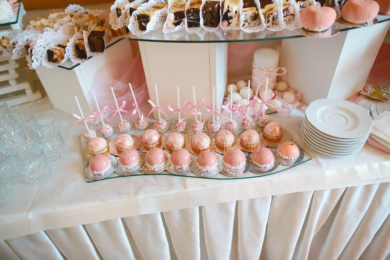Schließen Sie oben vom Behälter mit Verschiedenartigkeitsgebäck-Kuchen Tartlets des Loses köstlichen in Folge Frische rosa süße B lizenzfreie stockfotografie
