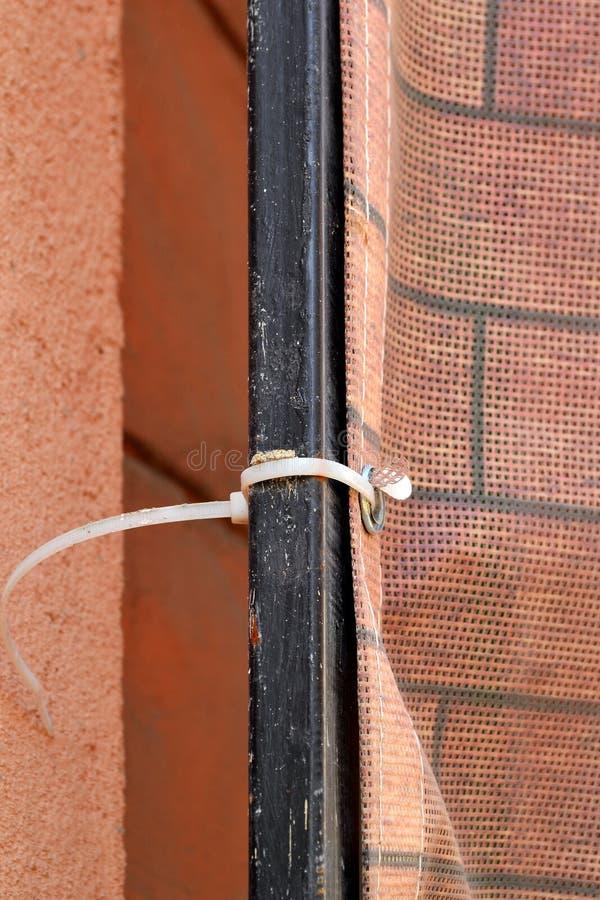 Schließen Sie oben vom Binden der Baumasche zum Baugerüst mit Plastikkabelbinder lizenzfreie stockfotografie