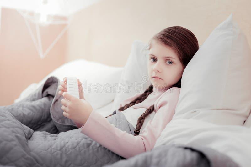 Schließen Sie oben vom blassen kranken Mädchen im Bett stockfotos