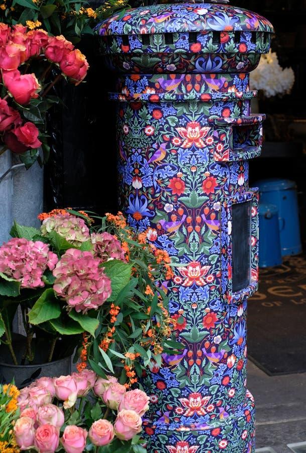 Schließen Sie oben vom Briefkasten, der im Freiheitsdruck bedeckt wird, gelegen im Blumenladen außerhalb der Freiheit von London- lizenzfreie stockbilder