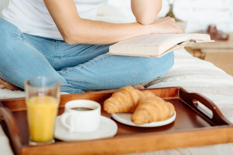 Schließen Sie oben vom Buch der jungen Frau Leseim Bett lizenzfreies stockfoto