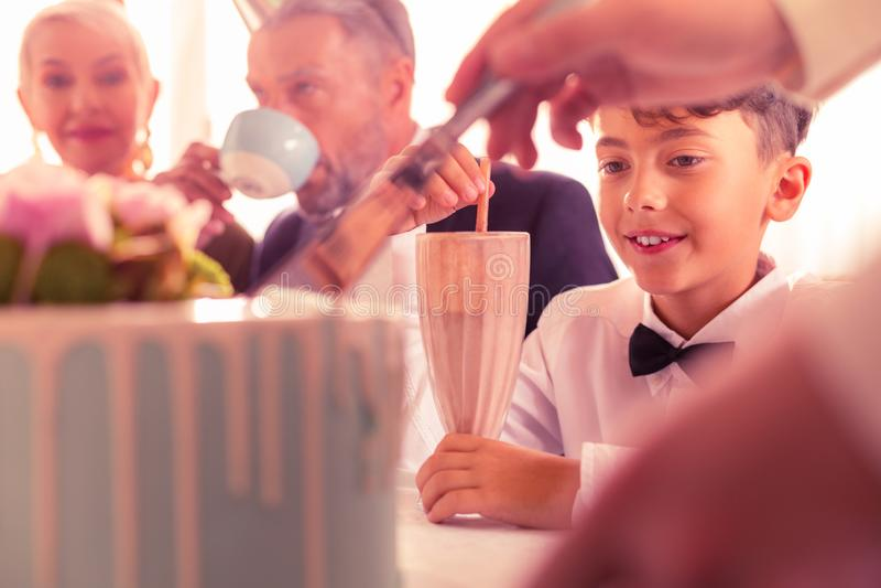 Schließen Sie oben vom dunkeläugigen Geburtstagsjungen, der nahe Großeltern sitzt lizenzfreies stockfoto
