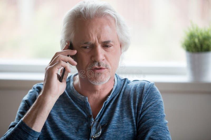 Schließen Sie oben vom ernsten gealterten Mann, der Telefongespräch hat stockfotografie