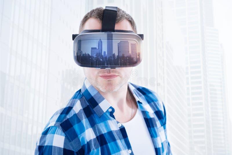 Schließen Sie oben vom ernsten Mann, der virtuelle Maske trägt stockbilder