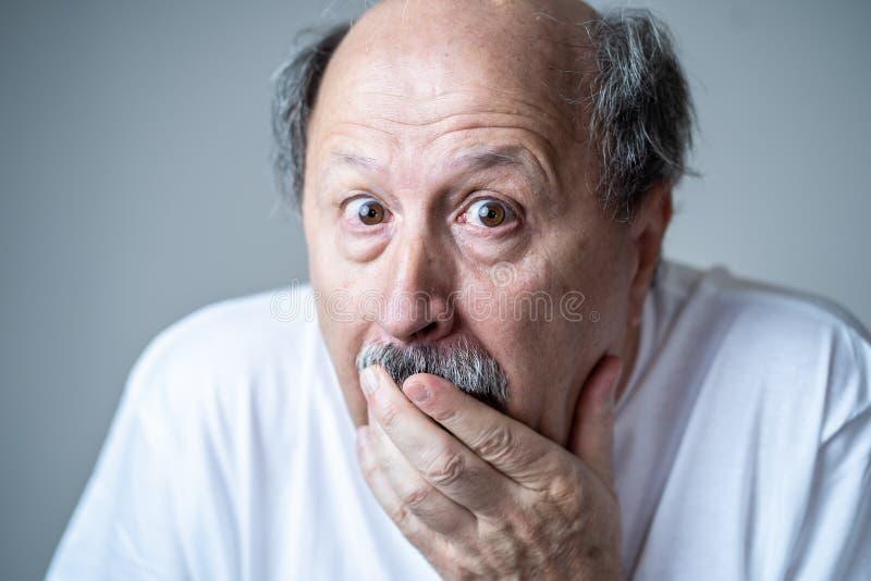 Schließen Sie oben vom erschrockenen und entsetzten älteren Mann, der in Furcht mit den Händen und Gesicht gestikuliert lizenzfreies stockfoto