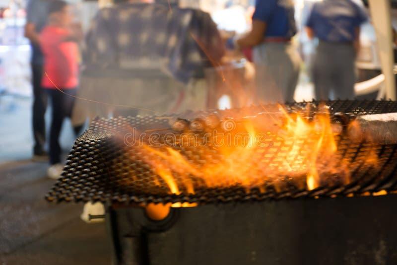 Schließen Sie oben vom Feuer, das Würste in der Straße während der italienischen Feier kocht lizenzfreie stockfotografie