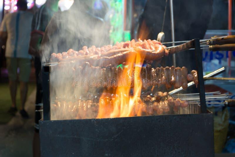 Schließen Sie oben vom Feuer, das Würste in der Straße während der italienischen Feier kocht lizenzfreies stockfoto