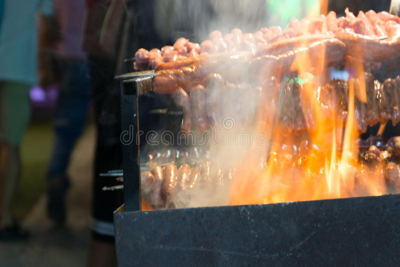 Schließen Sie oben vom Feuer, das Würste in der Straße während der italienischen Feier kocht stockfoto