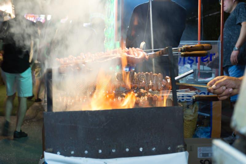 Schließen Sie oben vom Feuer, das Würste in der Straße während der italienischen Feier kocht lizenzfreie stockbilder
