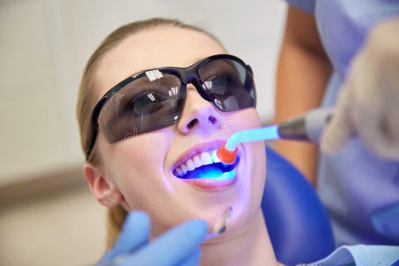 Schließen Sie oben vom Frauenpatienten mit zahnmedizinischem kurierendem Licht stockbilder
