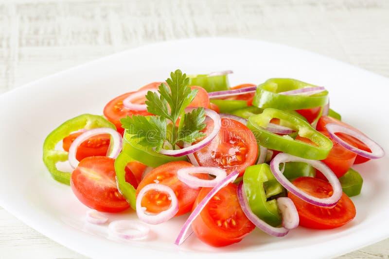 Schließen Sie oben vom frischen, organischen und gesunden Gemüsesalat mit Ringen der Kirschtomaten, der Petersilie, des grünen stockbilder