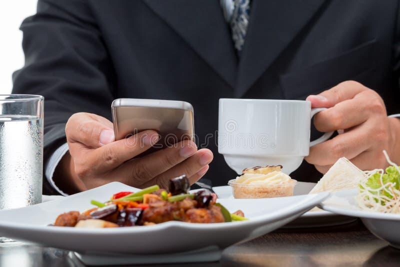 Schließen Sie oben vom Geschäftsmann, der die Nachrichten vom Handy beim Essen des Frühstücks überprüft stockbilder