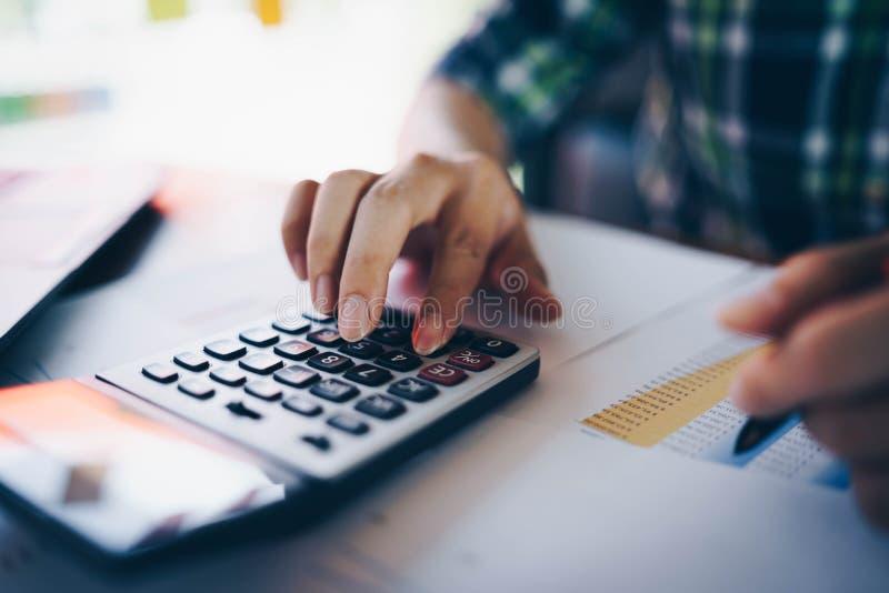 Schließen Sie oben vom Geschäftsmann oder von Buchhalter, die an Taschenrechner arbeiten, um kommerzielle Daten zu berechnen, und stockfotografie