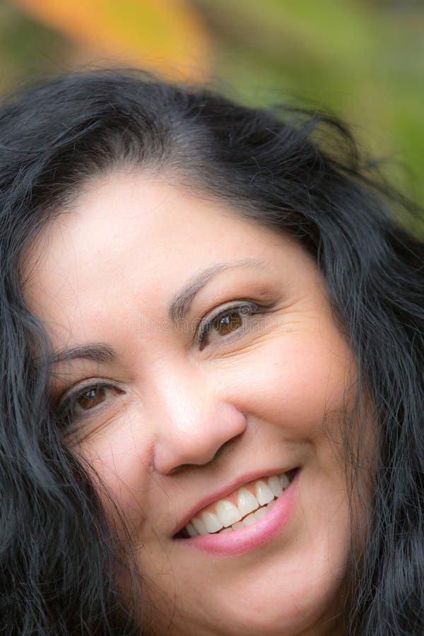 Schlie?en Sie oben vom Gesicht einer recht gl?cklichen Frau mit braunen Augen und dem schwarzen Haar stockbild
