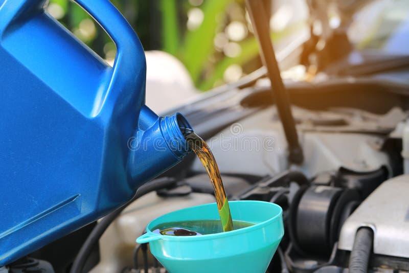 Schließen Sie oben vom Gießen des frischen Öls zum Automotor in Autoreparatur servi lizenzfreies stockfoto