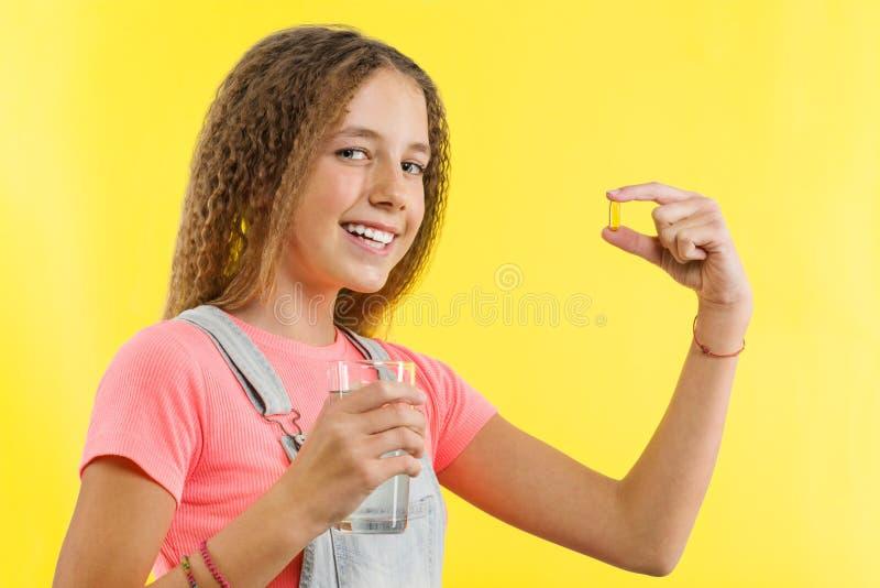 Schließen Sie oben vom glücklichen lächelnden jugendlich Mädchen, das Pille mit Lebertran omega-3 einnimmt und ein Glas Süßwasser lizenzfreies stockfoto