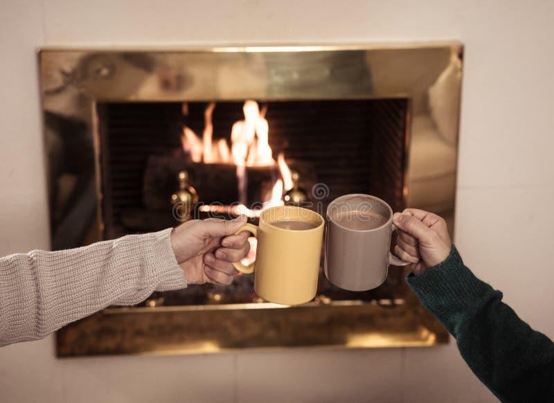 Schließen Sie oben vom glücklichen Paar, das heißes Getränk durch den Feuerplatz trinkt, der Liebe feiert und Winterurlaube mache stockbild