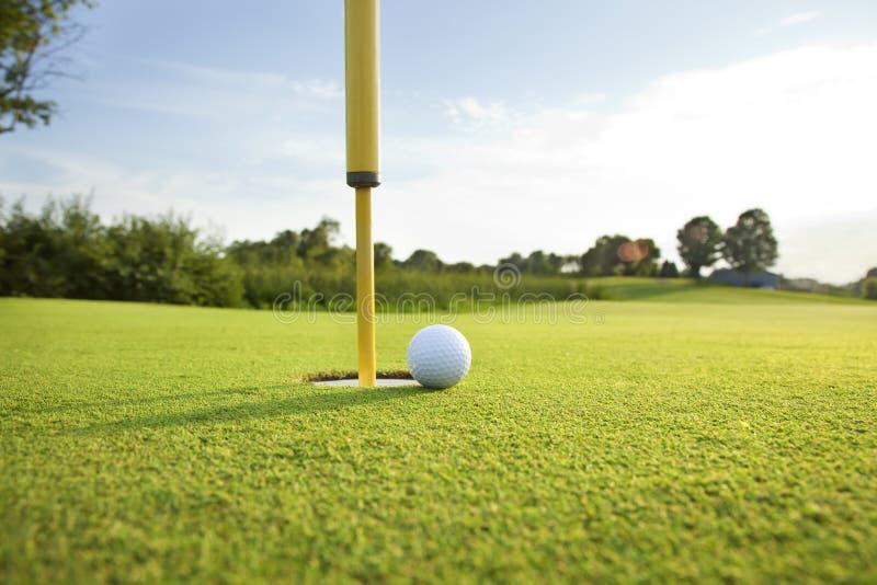 Schließen Sie oben vom Golfball auf dem Grün nahe dem Loch an einem sonnigen Nachmittag lizenzfreies stockfoto