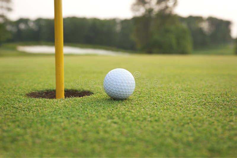 Schließen Sie oben vom Golfball auf einem grünen nahen Loch mit Stift lizenzfreies stockfoto