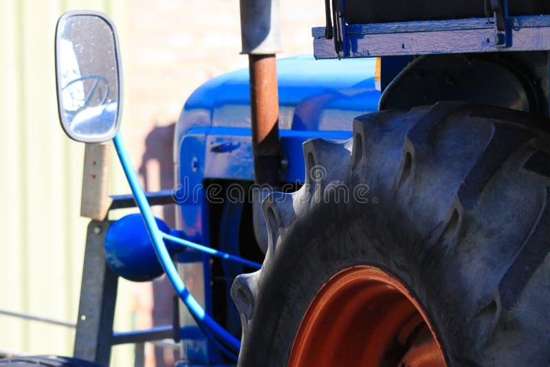 Schließen Sie oben vom großen Reifen des blauen alten alten antiken Traktors mit Rückspiegel und Maschine auf einem Bauernhof in  lizenzfreies stockbild