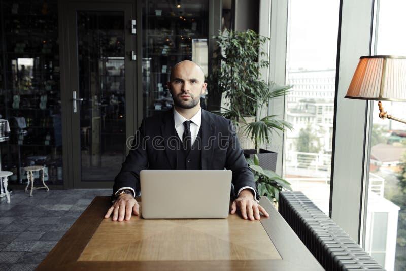 Schließen Sie oben vom hübschen Geschäftsmann und an Laptop im Restaurant arbeiten lizenzfreie stockbilder