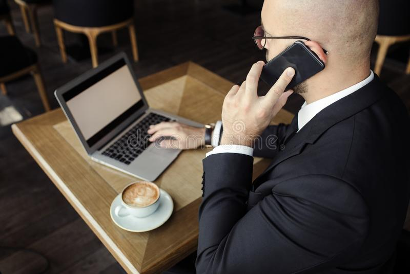 Schließen Sie oben vom hübschen Geschäftsmann und an Laptop im Restaurant arbeiten stockfoto