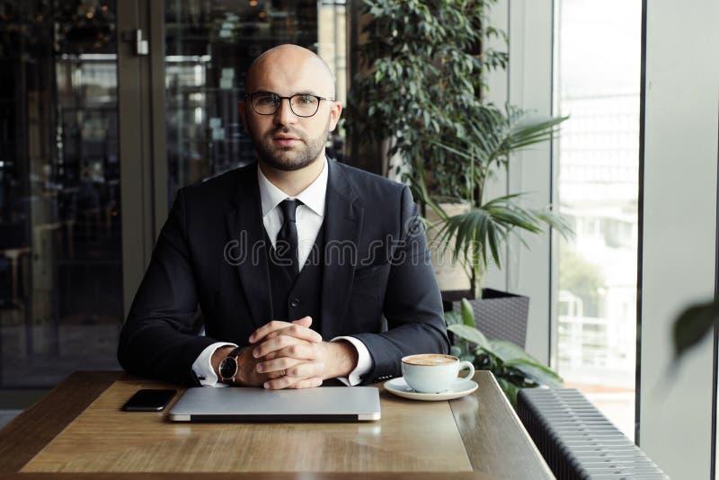 Schließen Sie oben vom hübschen Geschäftsmann und an Laptop im Restaurant arbeiten lizenzfreies stockfoto