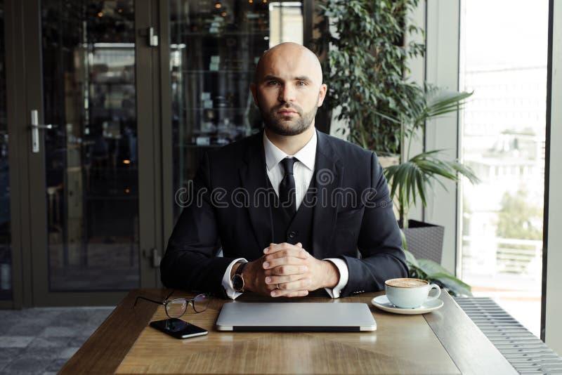 Schließen Sie oben vom hübschen Geschäftsmann und an Laptop im Restaurant arbeiten stockfotos