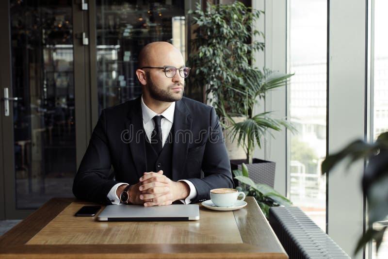 Schließen Sie oben vom hübschen Geschäftsmann und an Laptop im Restaurant arbeiten lizenzfreie stockfotos