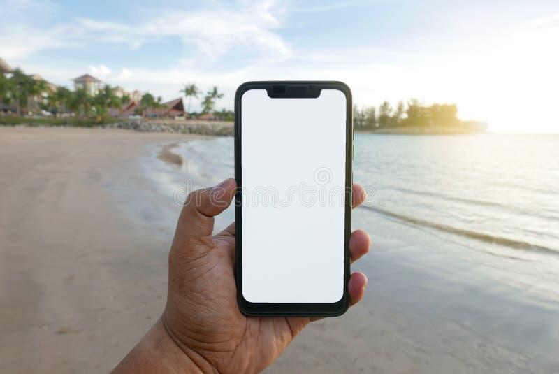Schließen Sie oben vom Handholdingtelefon mit weißem Schirm durch den Strand Smartphone mit Modell auf Hintergrundstrand und Hote lizenzfreie stockbilder