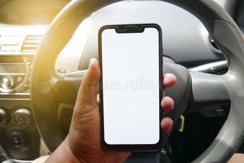Schließen Sie oben vom Handholdingtelefon mit weißem Schirm innerhalb eines Autos Smartphone mit Modell auf Hintergrund des Armat stockbilder