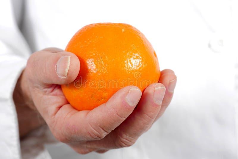 Schließen Sie oben vom Handmann, der Orange hält lizenzfreies stockbild