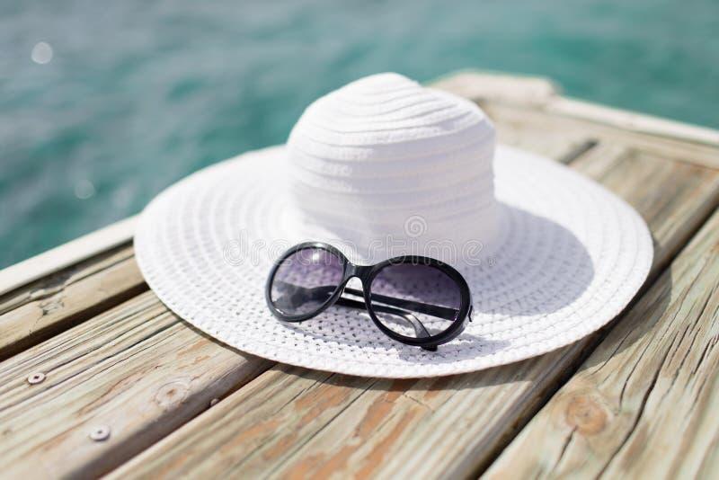 Schließen Sie oben vom Hut und von der Sonnenbrille an der Küste lizenzfreie stockfotos