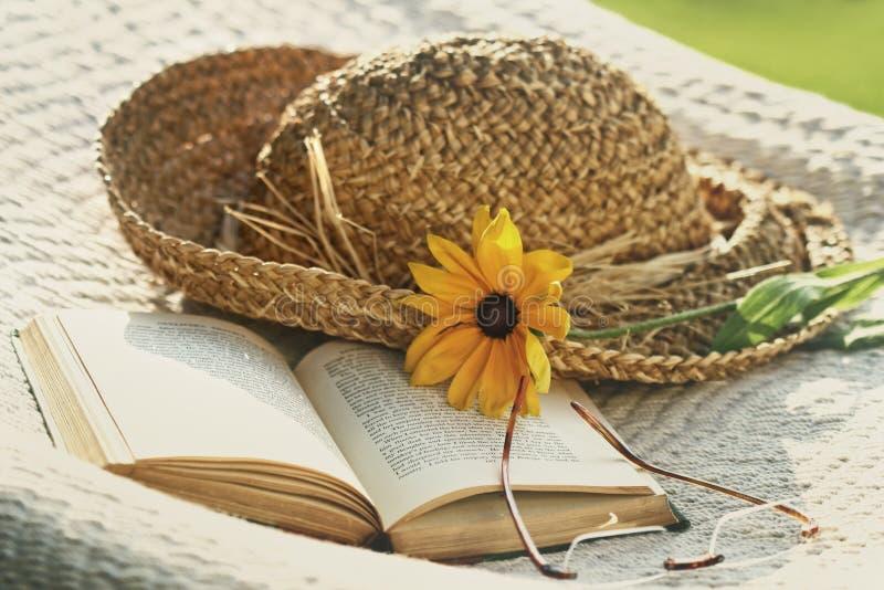 Schließen Sie oben vom Hut, von der Sonnenbrille und vom Buch auf einer Hängematte stockfotografie