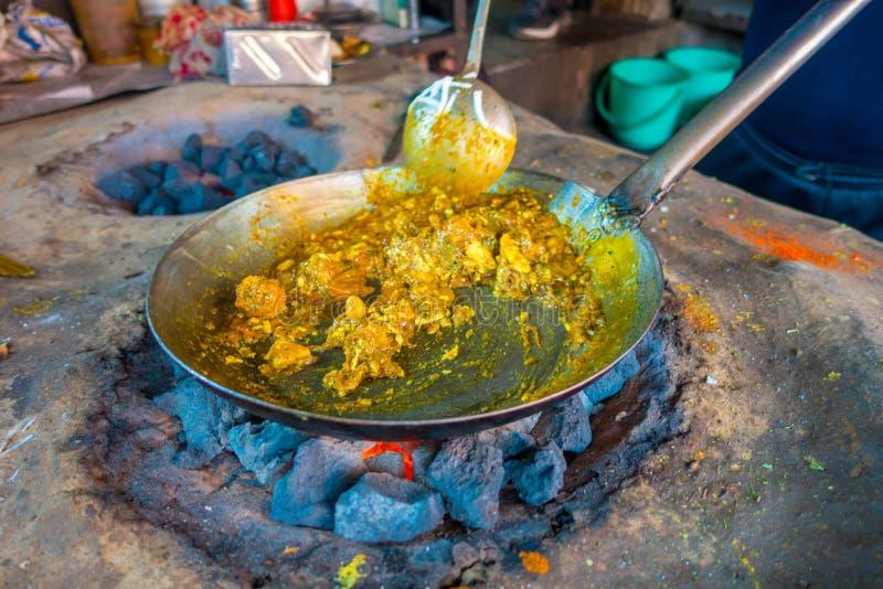 Schließen Sie oben vom indischen Lebensmittel, das in einem metallischen Behälter über weißglühenden Felsen in Jaipur, Indien gek lizenzfreies stockbild