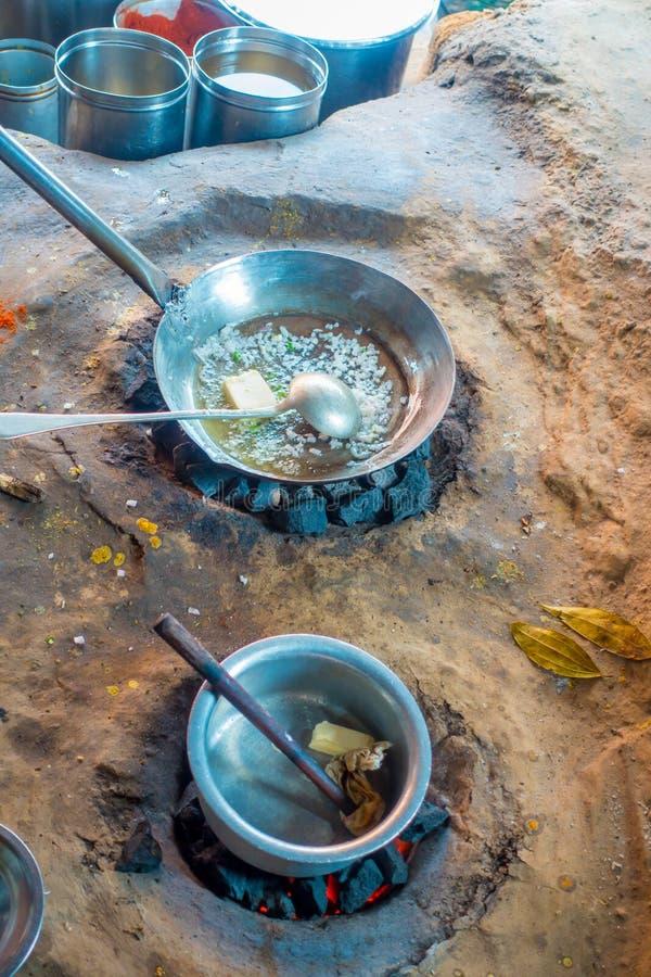 Schließen Sie oben vom indischen Lebensmittel innerhalb metallische Behälter im Boden, unter Verwendung der Kohle, zum in der Küc lizenzfreies stockbild