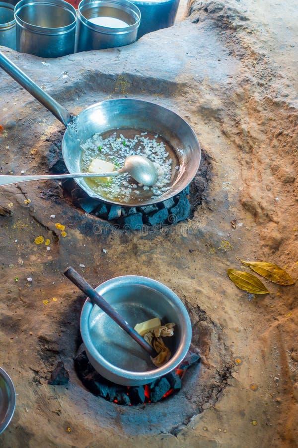 Schließen Sie oben vom indischen Lebensmittel innerhalb metallische Behälter im Boden, unter Verwendung der Kohle, zum in der Küc lizenzfreie stockbilder