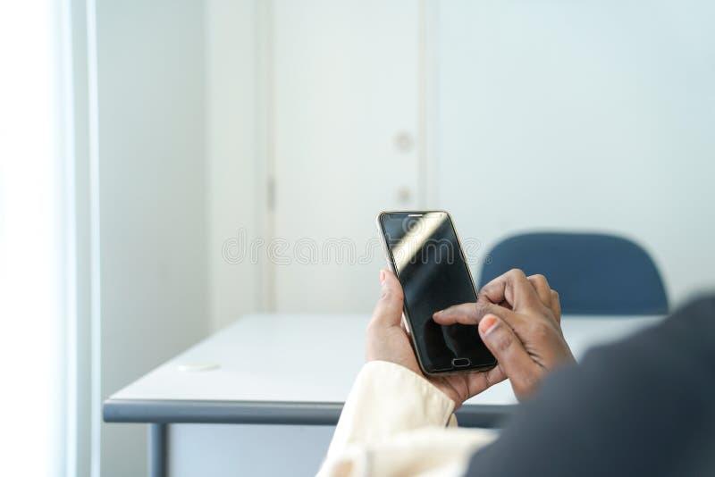Schließen Sie oben vom intelligenten Telefon mit weiblichen Hand-, Suchen oder des Sozialen Netzeskonzepten Bürohintergrund stockfoto