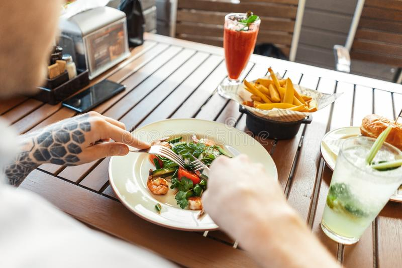 Schließen Sie oben vom jungen attraktiven Fleisch fressenden Salat am Straßencafé Rückseitige Ansicht stockbilder