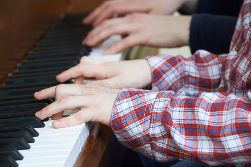 Schließen Sie oben vom Jungen, der Klavier-Duo mit Lehrer spielt lizenzfreies stockbild