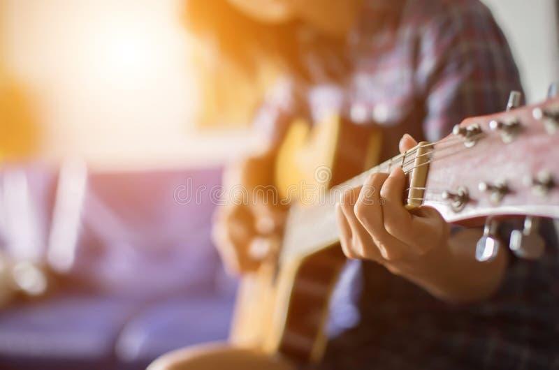 Schließen Sie oben vom jungen Hippie, den Frau Gitarre im Park übte, glücklich und genießen Sie, Gitarre zu spielen lizenzfreies stockfoto