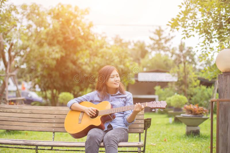 Schließen Sie oben vom jungen Hippie, den Frau Gitarre im Park übte, glücklich und genießen Sie, Gitarre zu spielen lizenzfreies stockbild