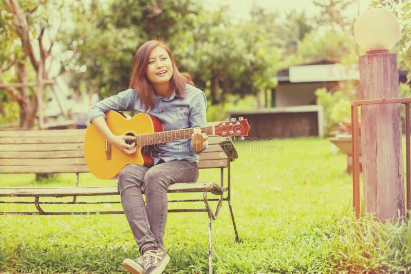Schließen Sie oben vom jungen Hippie, den Frau Gitarre im Park übte, glücklich und genießen Sie, Gitarre zu spielen stockbild